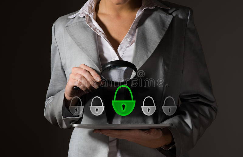 Concept of information security. Business woman with a magnifier safety checks on a Tablet PC royalty free stock photo
