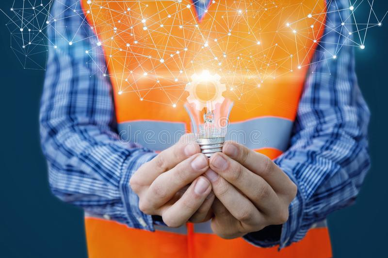 The concept is the innovative ideas in building industry. An engineer is holding a lightbulb with a bright cogwheel inside surrounded by wireless connections in stock photos