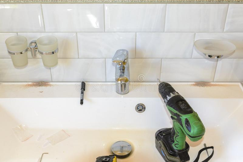 Concept installatie van toebehoren, zeepschotels en koppen voor de badkamers die een schroevedraaier gebruiken stock foto's
