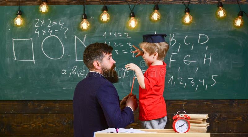 Concept instructif de conversation Enfant dans le professeur de écoute de chapeau licencié, tableau sur le fond, vue arrière prof photo stock