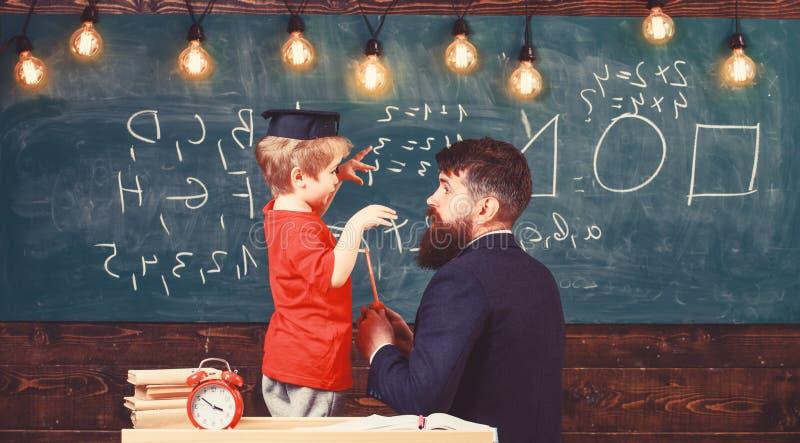 Concept instructif de conversation Enfant dans le professeur de ?coute de chapeau licenci?, tableau sur le fond, vue arri?re prof photo stock