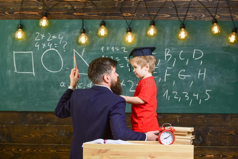 Concept instructif de conversation Le professeur avec la barbe, père enseigne le petit fils dans la salle de classe, tableau sur  photo stock