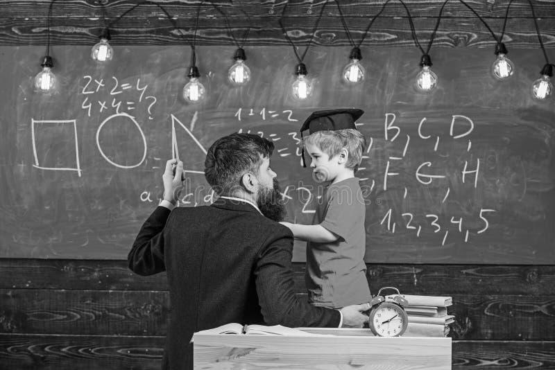 Concept instructif de conversation Le professeur avec la barbe, père enseigne le petit fils dans la salle de classe, tableau sur  photos stock