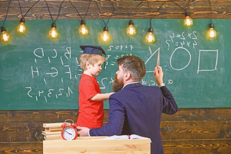 Concept instructif de conversation Le professeur avec la barbe, père enseigne le petit fils dans la salle de classe, tableau sur  photo libre de droits