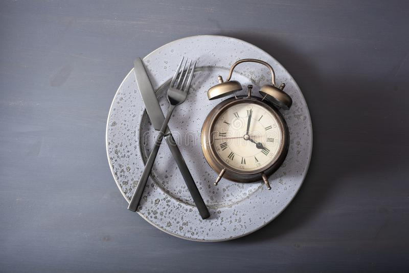 Concept of intermittent fasting, ketogenic diet, weight loss. alarmclock fork and knife on a plate royalty free stock photo