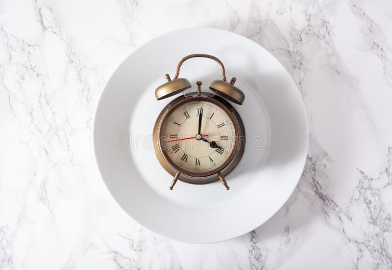 Concept of intermittent fasting, ketogenic diet, weight loss. alarmclock on a plate royalty free stock photo