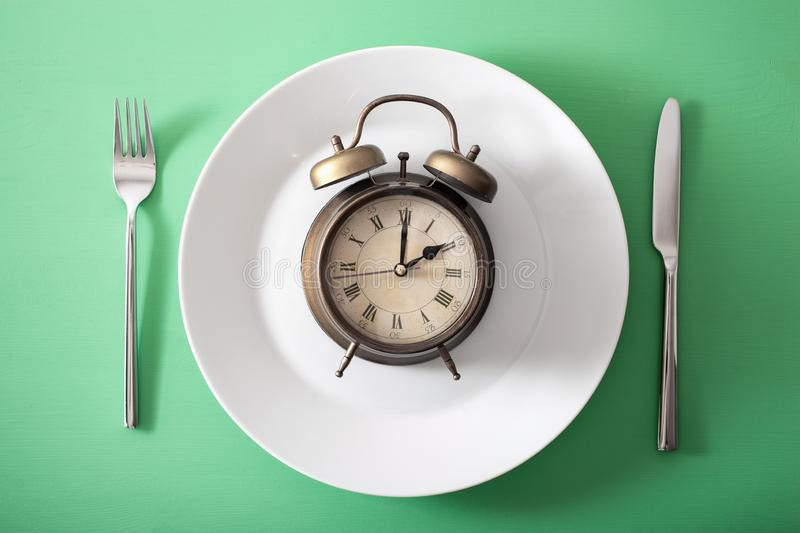 Concept of intermittent fasting, ketogenic diet, weight loss. alarmclock on a plate stock images