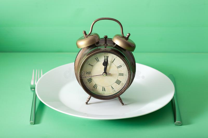 Concept of intermittent fasting, ketogenic diet, weight loss. alarmclock on a plate stock photography