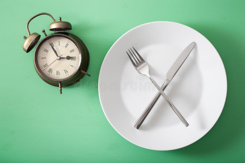 Concept of intermittent fasting, ketogenic diet, weight loss. fork and knife crossed on a plate and alarmclock royalty free stock image