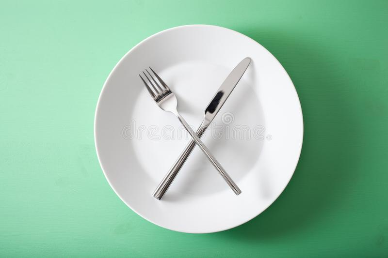 Concept of intermittent fasting and ketogenic diet, weight loss. fork and knife crossed on a plate stock photos