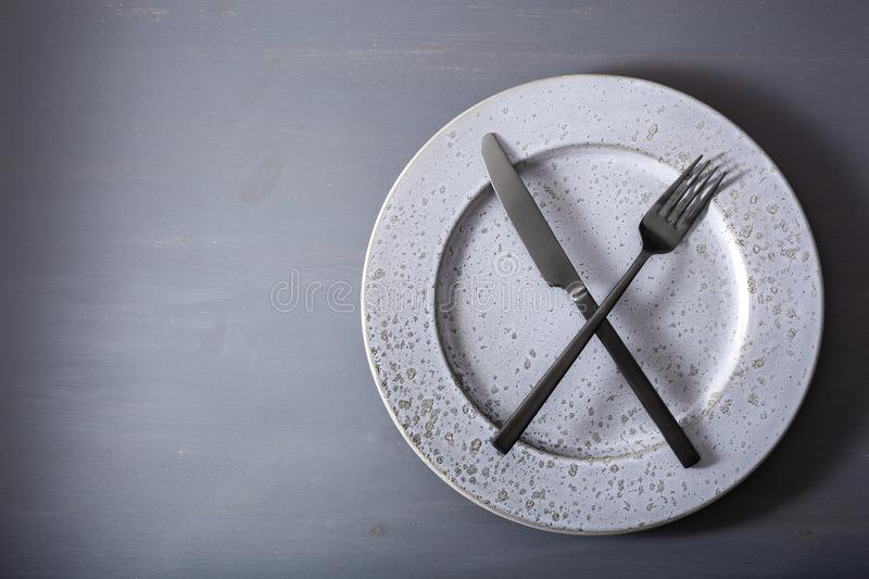 Concept of intermittent fasting and ketogenic diet, weight loss. fork and knife crossed on a plate stock photo