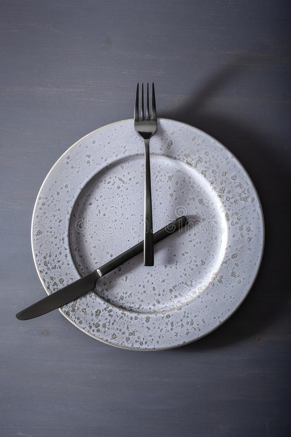 Concept of intermittent fasting and ketogenic diet, weight loss. fork and knife crossed on a plate royalty free stock photography