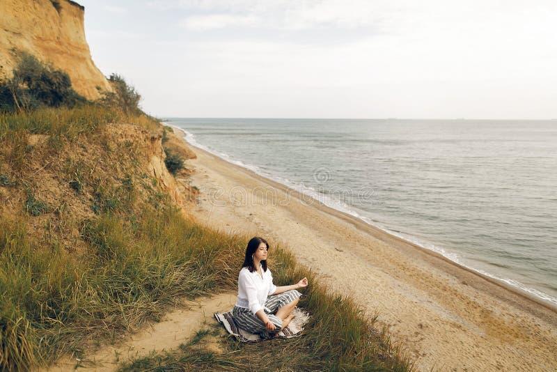 Concept international de jour de yoga Yoga de pratique de jeune belle femme sur la plage, se reposant en herbe et sable Fille de  photographie stock libre de droits
