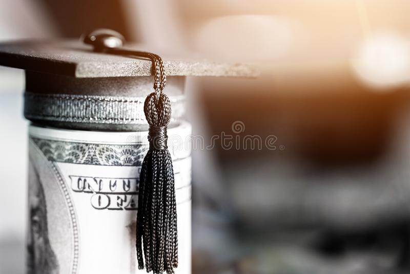 Concept of international graduate study, graduation black cap on pile of foreign money US dollars money on blur background. stock image