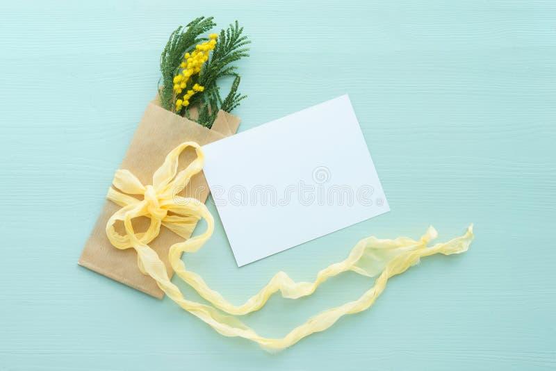 Concept internationale de Mimosabrunch van de vrouwen` s dag in Kraftpapier-envelopzak op een blauwe boog als achtergrond van gel stock foto's