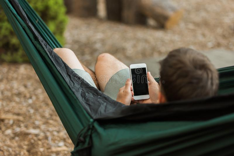 Man working on smartphone in hammock in forest royalty free stock photo