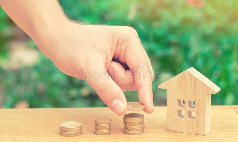 Concept investment in real estate. Saving money to buy a new home. Wooden house and stacks of coins from small to large. stock photography