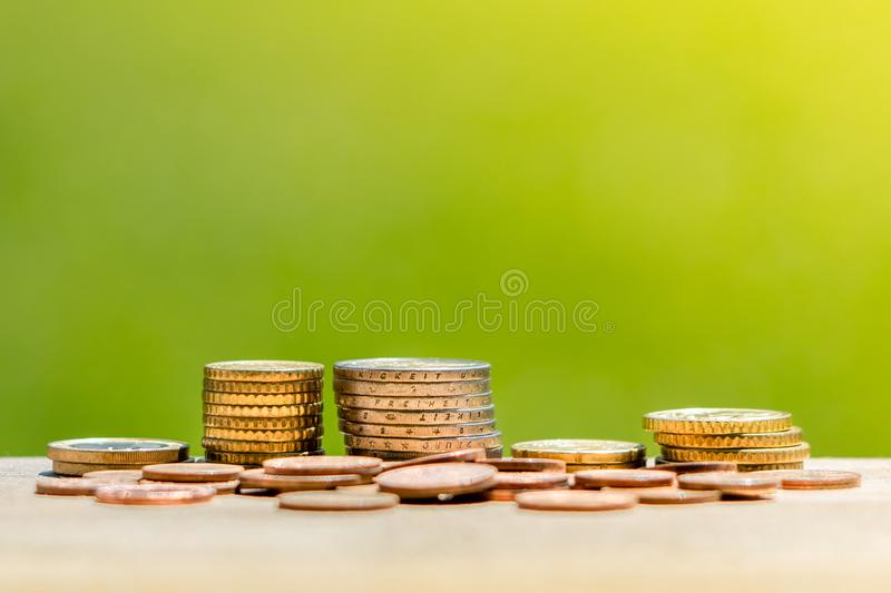 Concept of investment and saving money. Pile of euro coins on wooden table stock photos