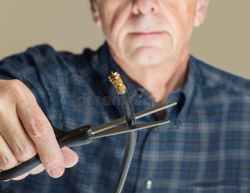 Concept isolated photo of cutting cable cord. Cutting the cable connection to coax connector illustrating retired people cancelling cable TV service stock photography