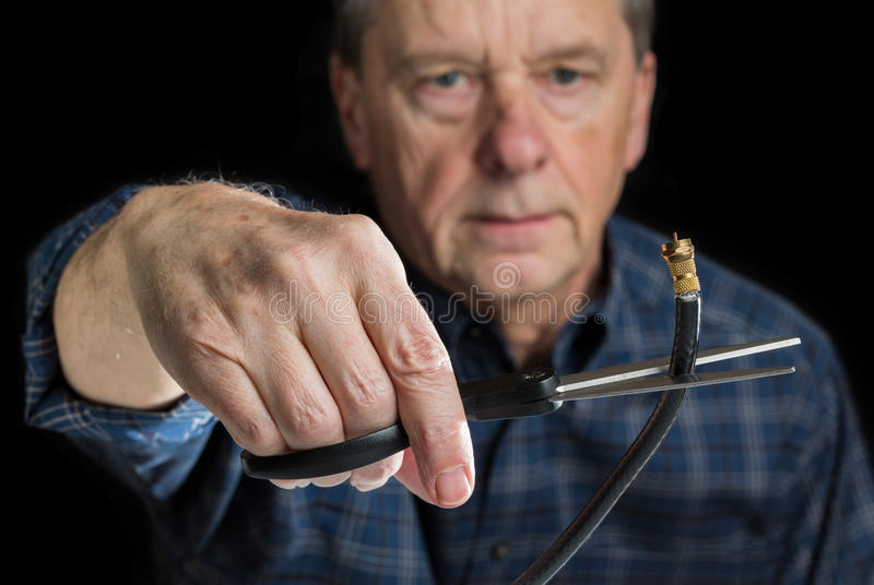 Concept isolated photo of cutting cable cord. Cutting the cable connection to coax connector illustrating retired people cancelling cable TV service royalty free stock image
