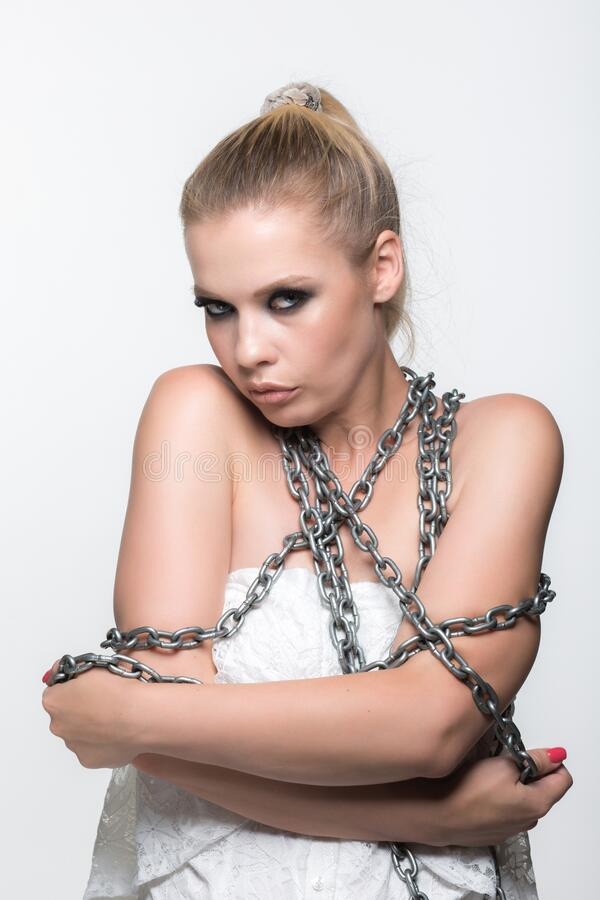 The concept of isolation from society. Young girl in chains in white clothes on a white background. The concept of self-isolation from society royalty free stock photo