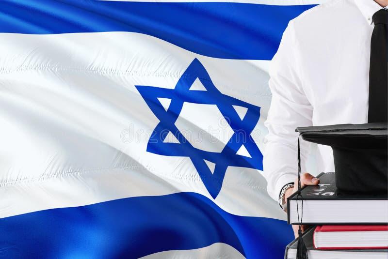 Concept israélien réussi d'éducation d'étudiant Tenir les livres et le chapeau d'obtention du diplôme au-dessus du fond de drapea photographie stock libre de droits
