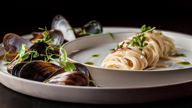 The concept of Italian cuisine. Pasta with cream sauce, pesto and seafood, mussels. European cuisine. Serving dishes stock photography