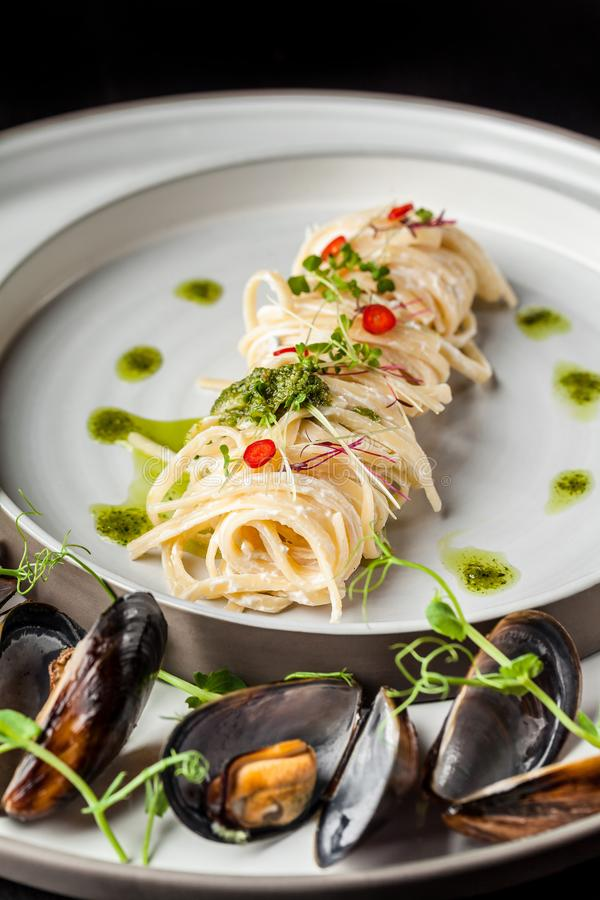 The concept of Italian cuisine. Pasta with cream sauce, pesto and seafood, mussels. European cuisine. Serving dishes royalty free stock images