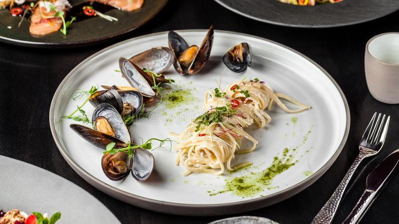 The concept of Italian cuisine. Pasta with cream sauce, pesto and seafood, mussels. European cuisine. Serving dishes stock images