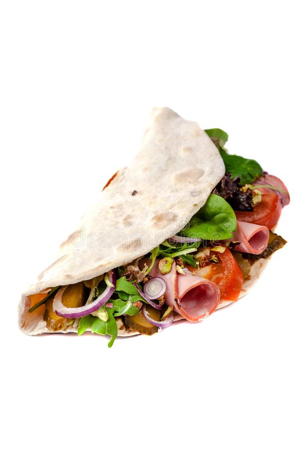The concept of Italian cuisine. Piadina with ham, tomatoes, lettuce mix, pistachios and cucumbers on white background. Isolate stock images