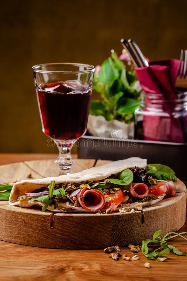 Concept Italian cuisine. Piadina with ham, tomatoes, mix lettuce, pistachios, cucumbers on wooden board. Glass of red wine. On the table. Beautiful serving royalty free stock images