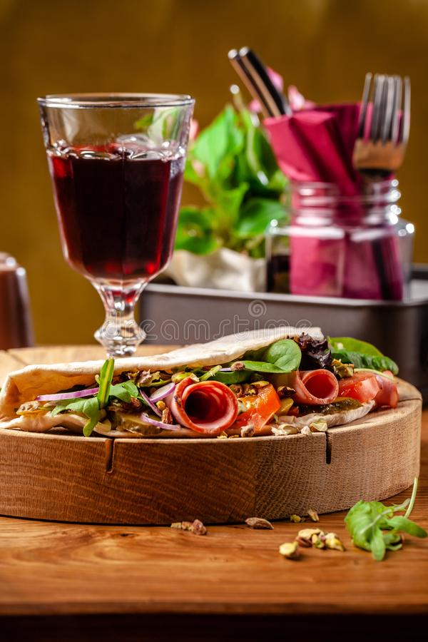 Concept Italian cuisine. Piadina with ham, tomatoes, mix lettuce, pistachios, cucumbers on wooden board. Glass of red wine. On the table. Beautiful serving stock images