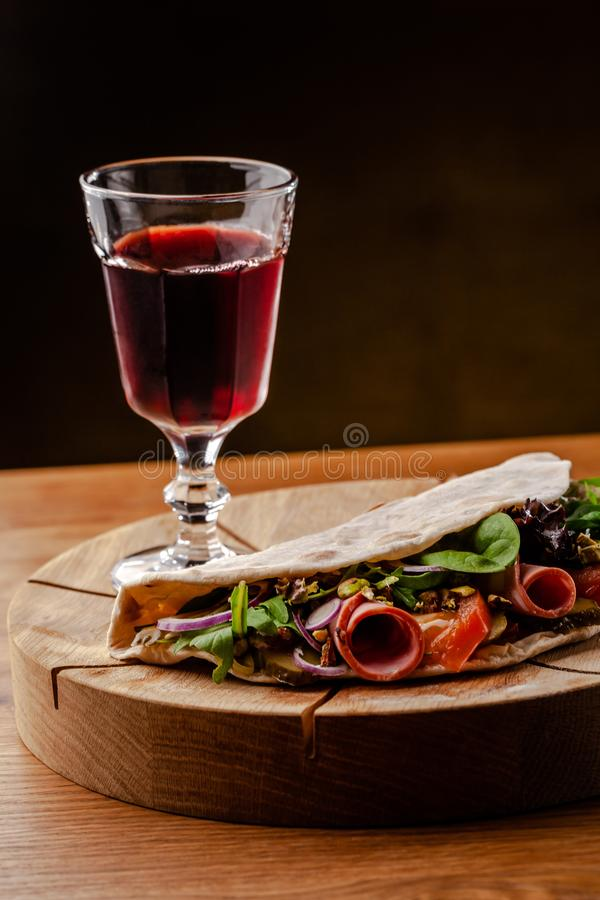 Concept Italian cuisine. Piadina with ham, tomatoes, mix lettuce, pistachios, cucumbers on wooden board. Glass of red wine. On the table. Beautiful serving stock photos