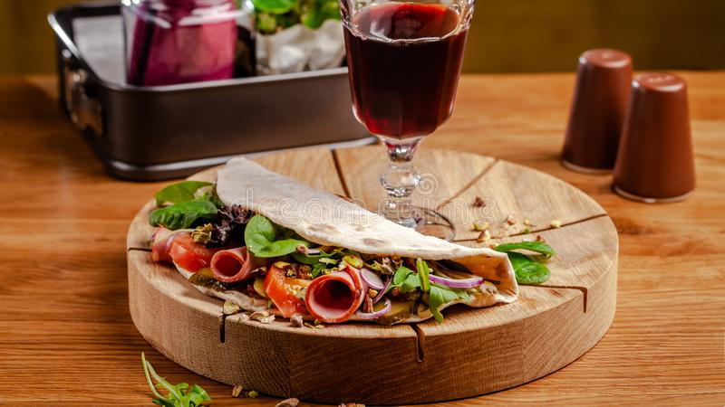 Concept Italian cuisine. Piadina with ham, tomatoes, mix lettuce, pistachios, cucumbers on wooden board. Glass of red wine. On the table. Beautiful serving royalty free stock photo