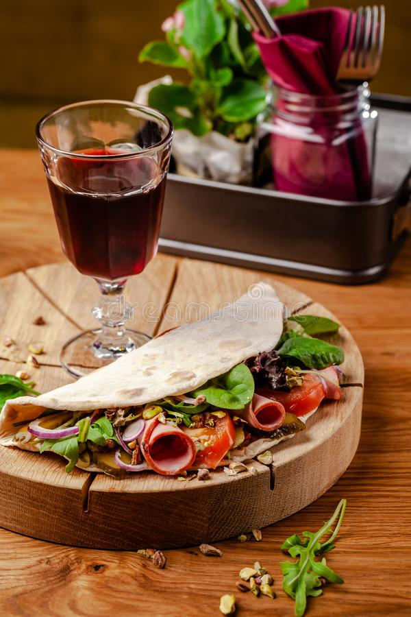 Concept Italian cuisine. Piadina with ham, tomatoes, mix lettuce, pistachios, cucumbers on wooden board. Glass of red wine. On the table. Beautiful serving royalty free stock image