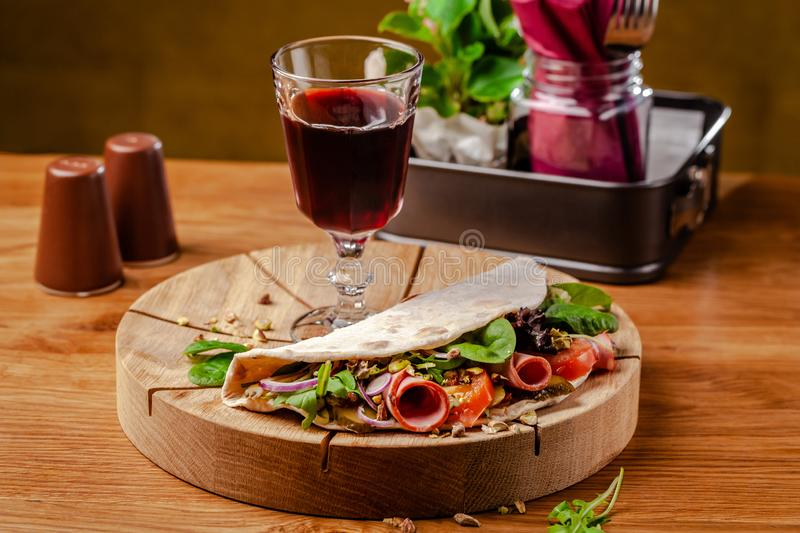 Concept Italian cuisine. Piadina with ham, tomatoes, mix lettuce, pistachios, cucumbers on wooden board. Glass of red wine. On the table. Beautiful serving stock photo