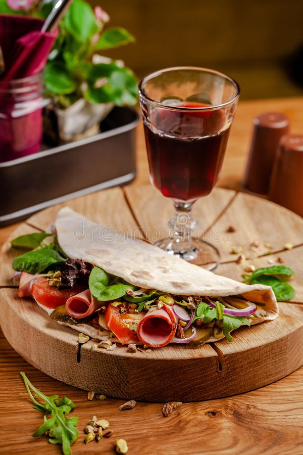 Concept Italian cuisine. Piadina with ham, tomatoes, mix lettuce, pistachios, cucumbers on wooden board. Glass of red wine. On the table. Beautiful serving stock image