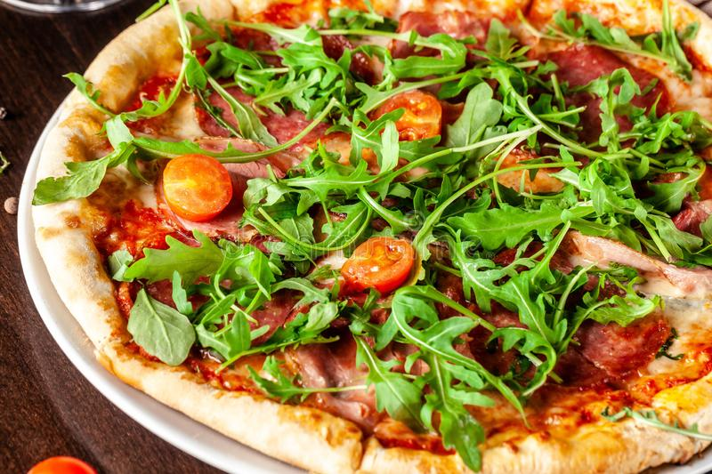 The concept of Italian cuisine. Pizza with sausage salami, bacon, cherry tomatoes and arugula stock photography
