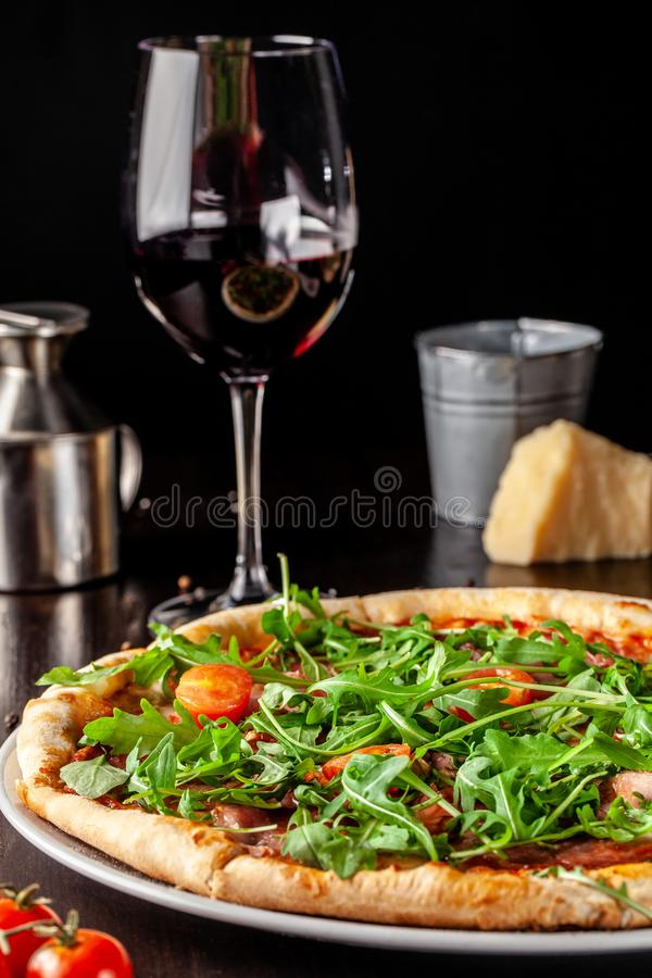 The concept of Italian cuisine. Pizza with sausage salami, bacon, cherry tomatoes and arugula. Next to table is glass of wine. The concept of Italian cuisine royalty free stock images