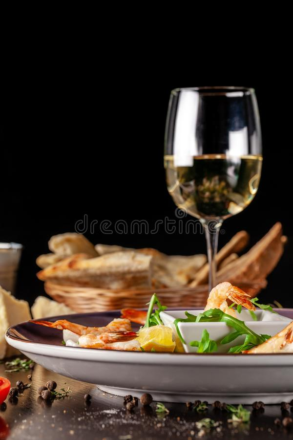 The concept of Italian cuisine. Tiger prawns on rice chips in a creamy sauce. Arugula salad and lemon. On table is glass of wine. The concept of Italian cuisine stock photos