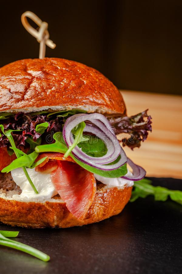 Concept of Italian home cooking. Burger with beef and pork meat cutlet, mozzarella cheese, salami sausage, parma, arugula royalty free stock photography
