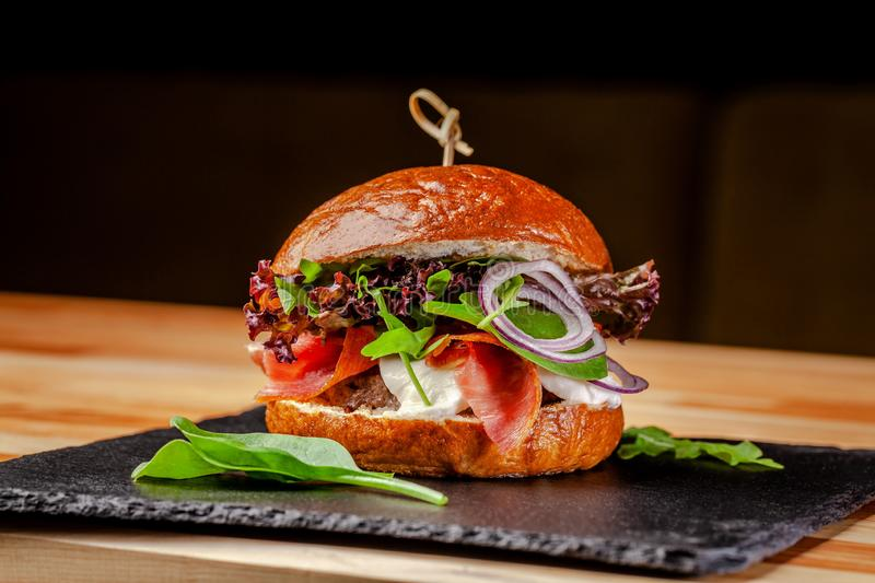 Concept of Italian home cooking. Burger with beef and pork meat cutlet, mozzarella cheese, salami sausage, parma, arugula stock photo