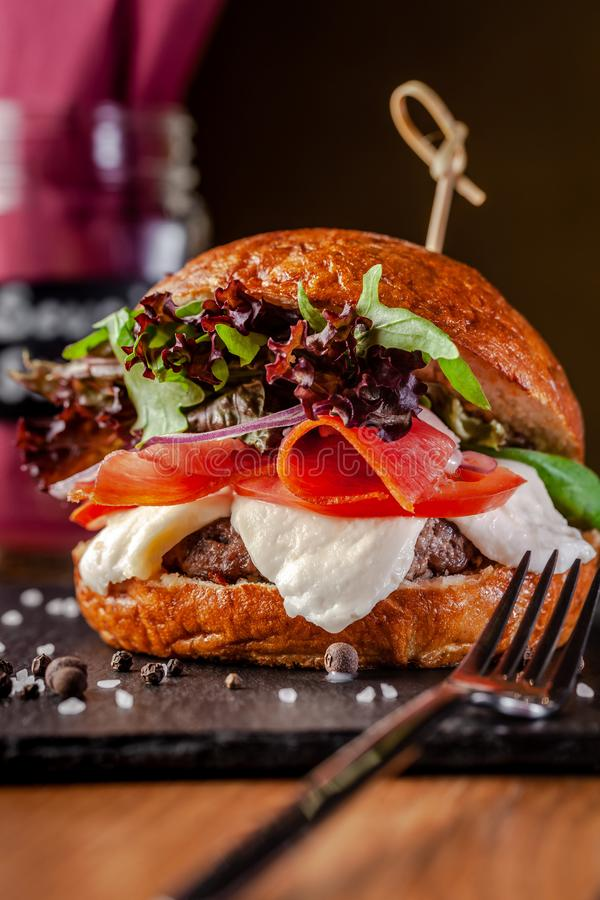 Concept of Italian home cooking. Burger with beef and pork meat cutlet, mozzarella cheese, salami sausage, parma, arugula stock photography