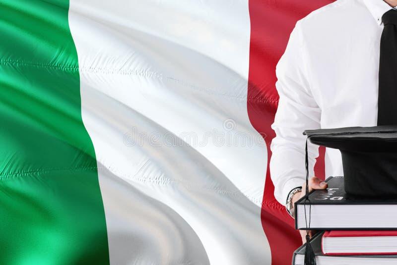 Concept italien réussi d'éducation d'étudiant Tenir les livres et le chapeau d'obtention du diplôme au-dessus du fond de drapeau  image libre de droits