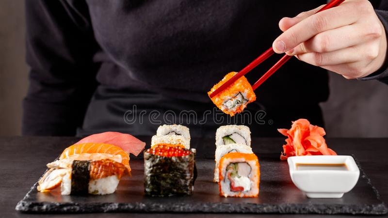 The concept of Japanese cuisine. A girl holds a red Chinese chopsticks and eat sushi in a restaurant. background image. Popular Japanese food. copy space royalty free stock photos