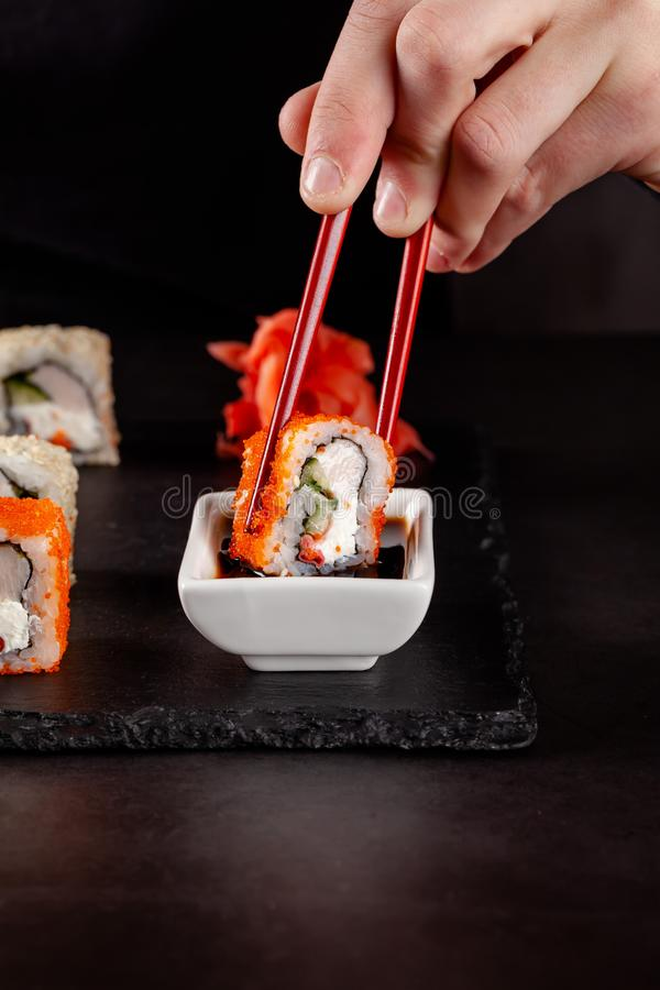 The concept of Japanese cuisine. A girl holds a red Chinese chopsticks and eat sushi in a restaurant. background image. Popular. Japanese food. copy space stock photo
