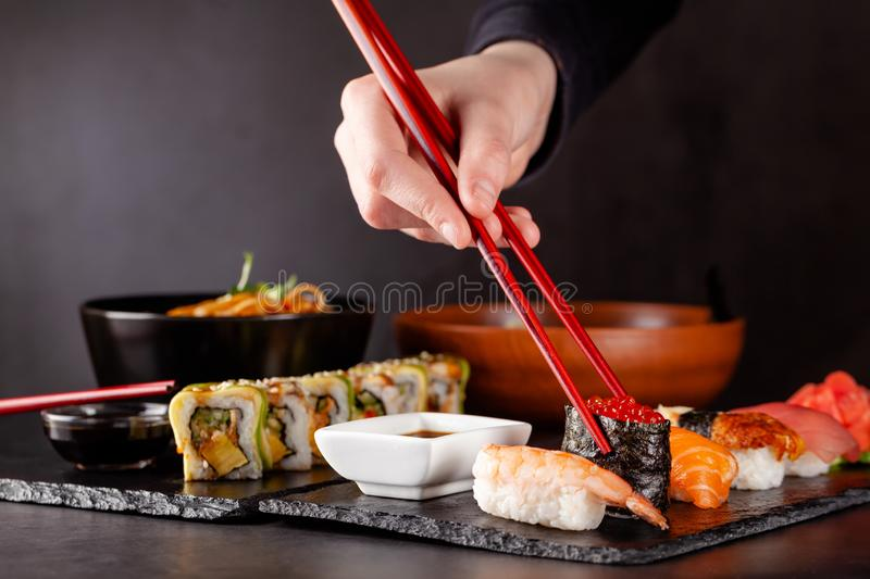 The concept of Japanese cuisine. A girl holds a red Chinese chopsticks and eat sushi in a restaurant. background image. Popular. Japanese food. copy space stock photos