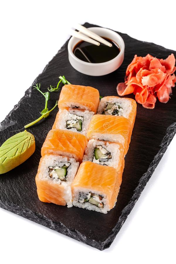 The concept of Japanese cuisine. Rolls with salmon, feta cheese, cucumber. Near soy sauce, ginger and wasabi. Modern serving stock images