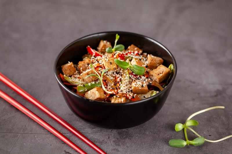 The concept of Japanese cuisine. Vegetarian noodles with tofu cheese and vegetables in a black ceramic plate. Red Chinese sticks. Copy space stock image