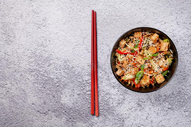 The concept of Japanese cuisine. Vegetarian noodles with tofu cheese and vegetables in a black ceramic plate. Red Chinese sticks. Copy space royalty free stock image